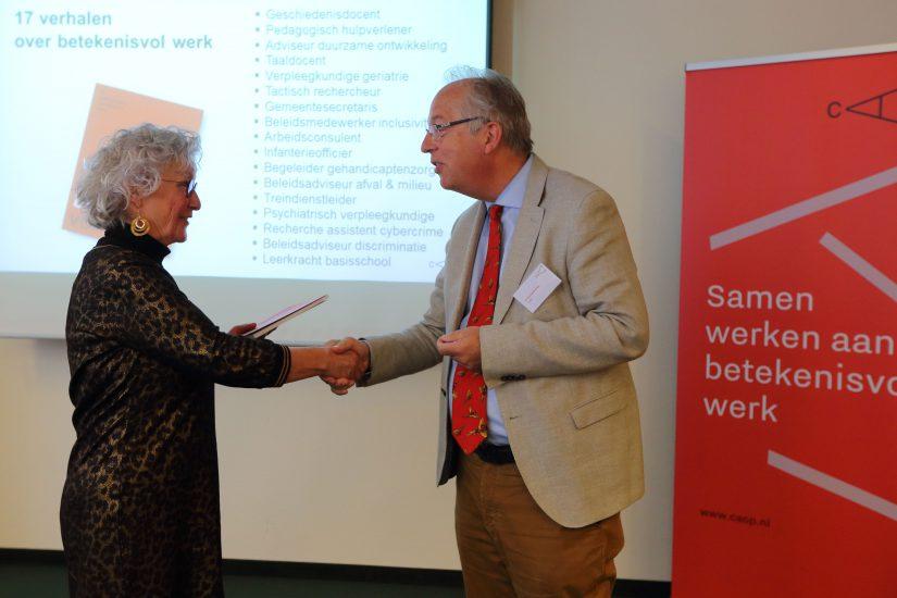 Directeur/bestuurder Philip Geelkerken overhandigt het boek '17 verhalen over betekenisvol werk' aan Anneke Jansen, taaldocent en één van de geïnterviewden uit het boek
