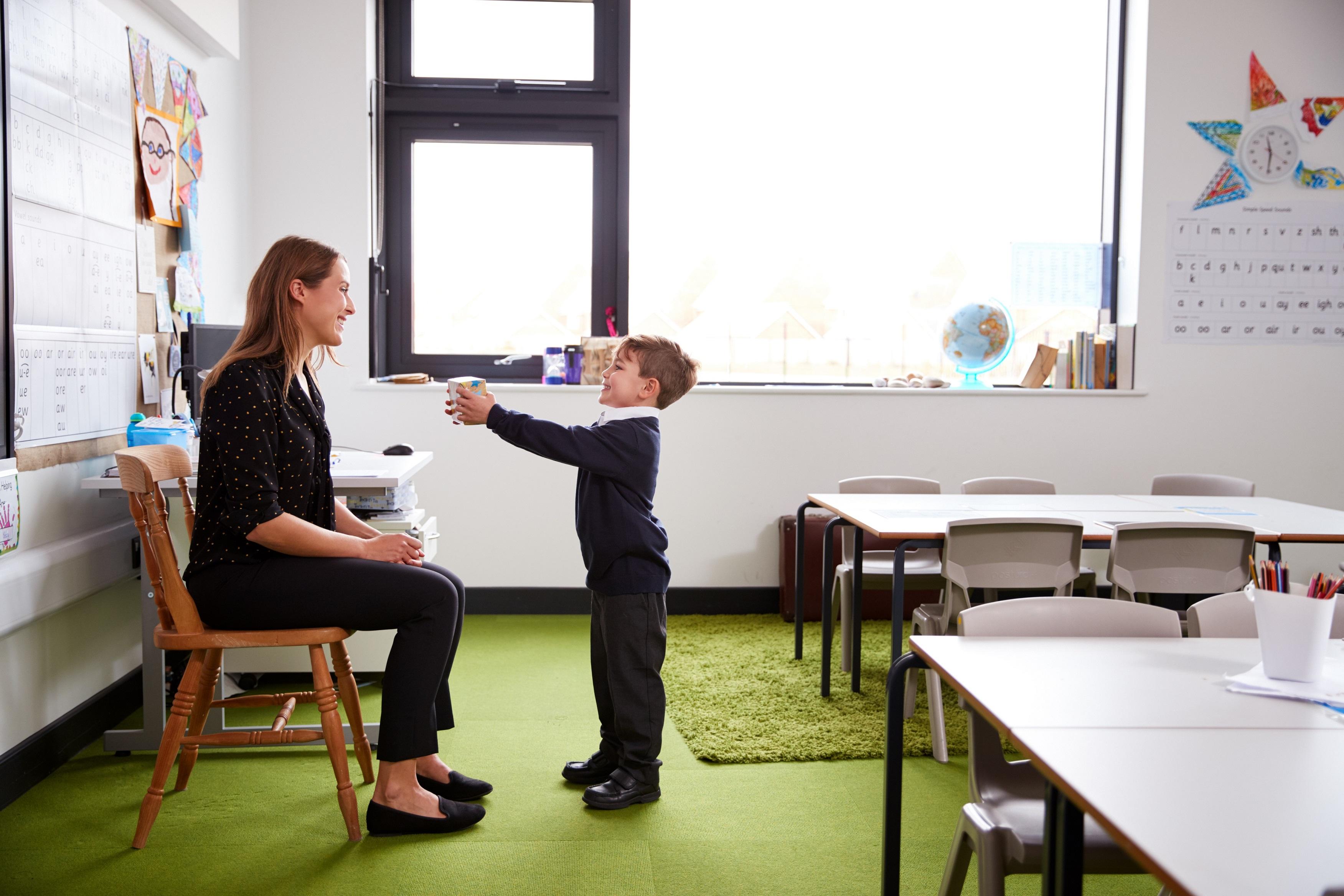 Jongetje geeft aan haar lerares een cadeau als bedankje