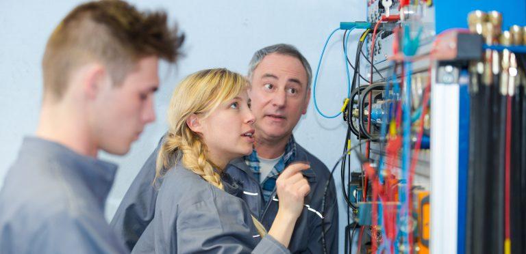 Een oudere werknemer legt iets uit over elektriciteit
