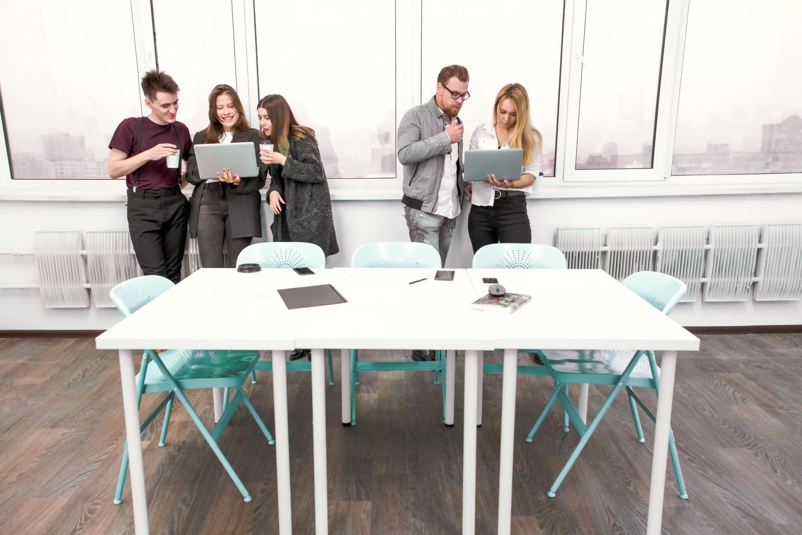 Vijf mensen praten met elkaar met hun laptop in handen