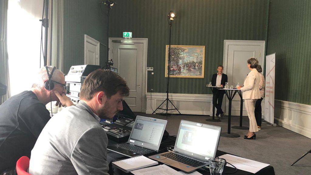 Twee medewerkers van het CAOP op de voorgrond die verantwoordelijk zijn voor de techniek met daarachter de sprekers van de webinar
