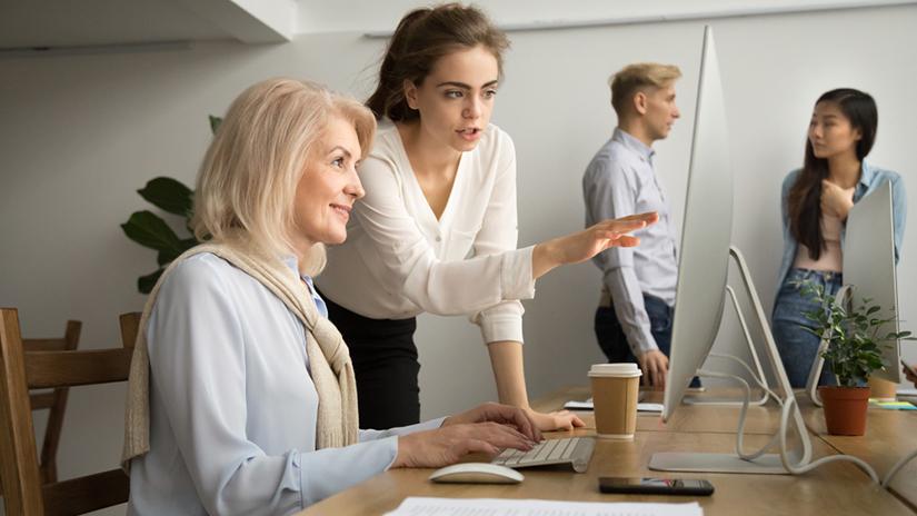Jonge werknemer legt iets uit aan oudere werknemer
