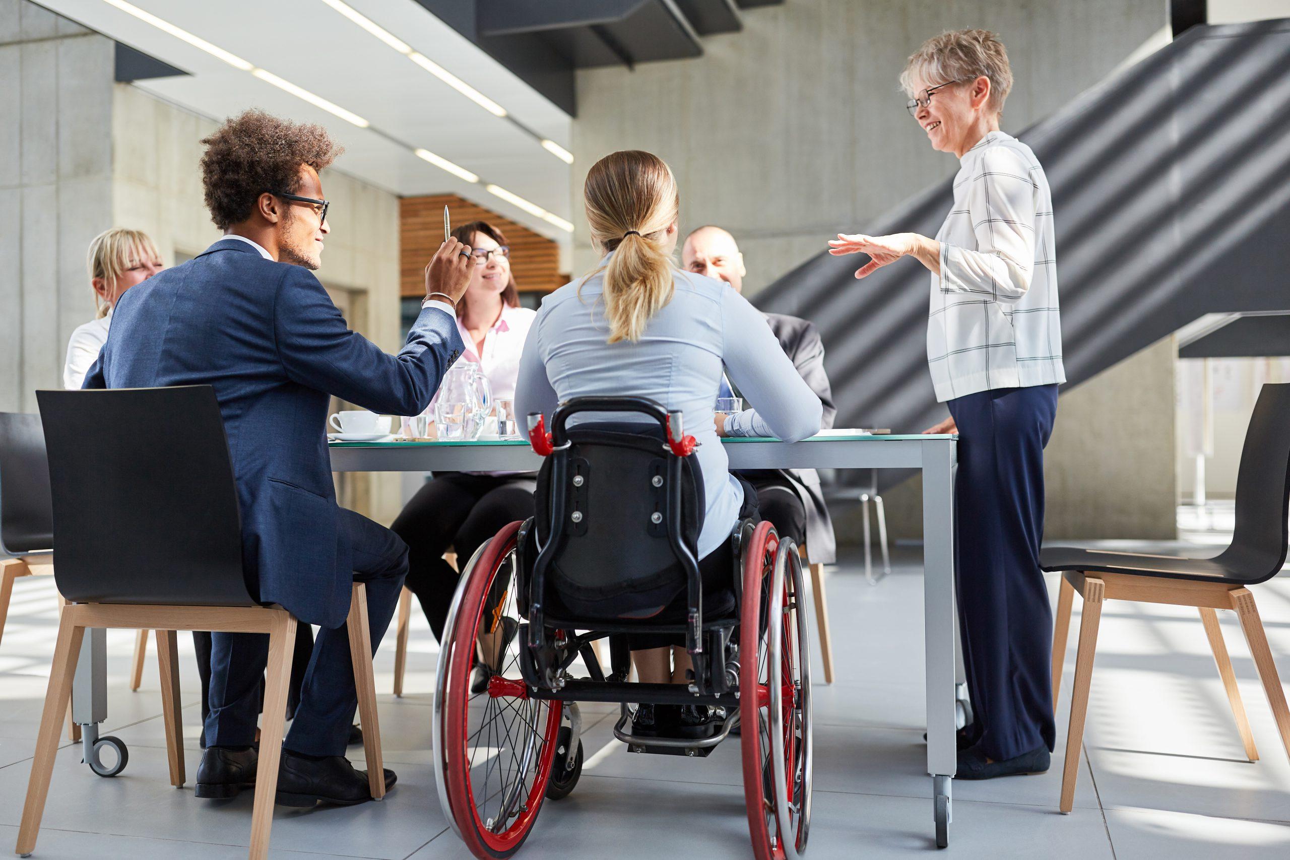 Mensen rond een tafel van wie 1 in een rolstoel