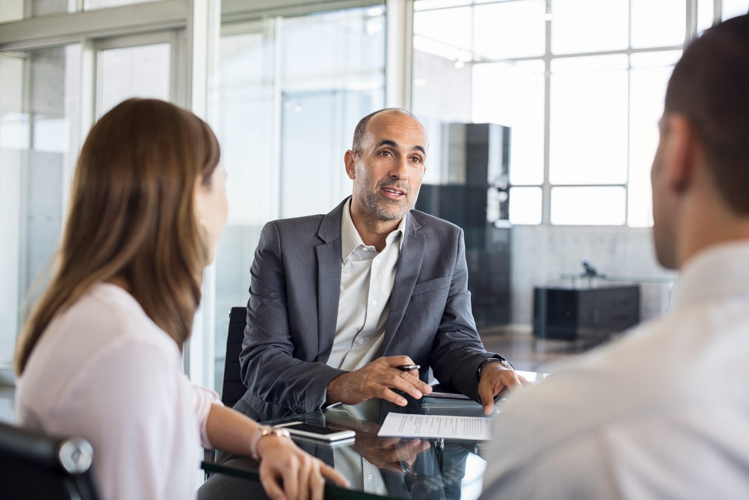 Drie mensen rond een tafel in gesprek