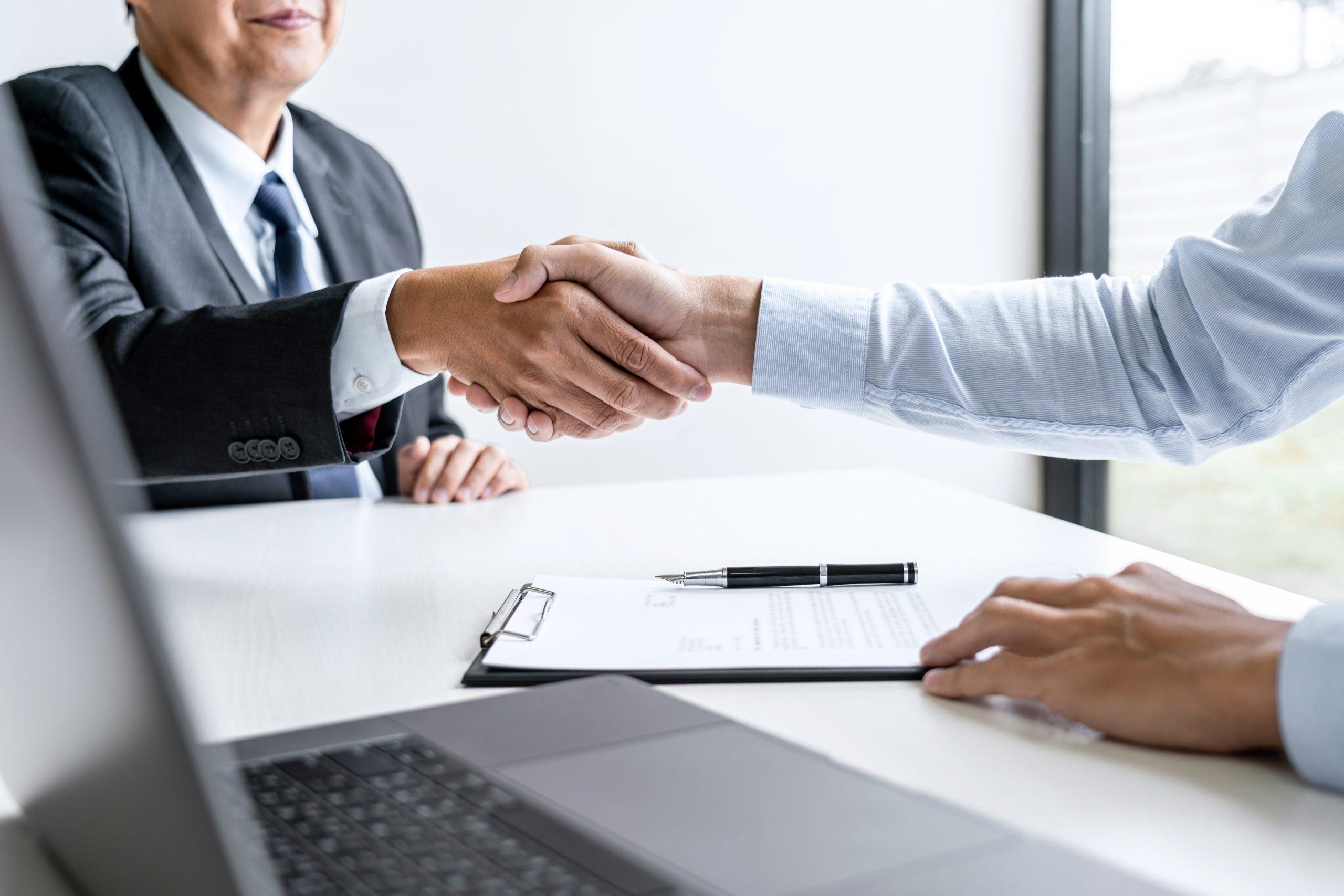 Twee mensen geven elkaar een hand na het tekenen van een overeenkomst