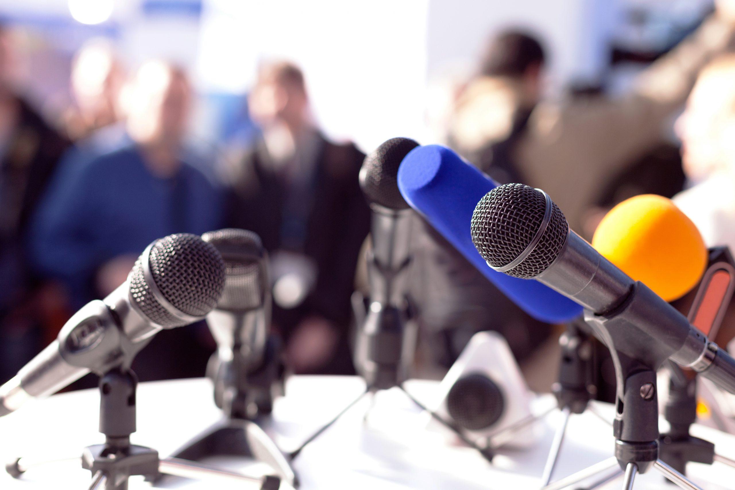 Diverse microfoons die klaarstaan voor een persconferentie. Op de achtergrond zijn mensen te zien die de persconferentie willen bijwonen.