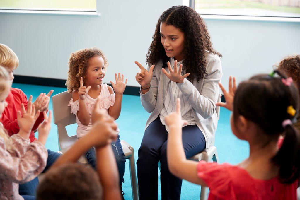 Leraar zit in een kringetje met jonge leerlingen en leert ze tellen